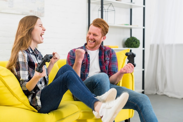 Retrato, de, excitado, par jovem, desfrutando, jogando videogame, casa