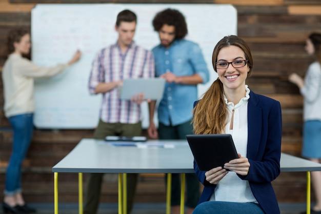 Retrato de executivo de negócios feminino com tablet digital sentado no escritório