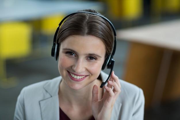 Retrato de executivos de negócios, falando no fone de ouvido no escritório