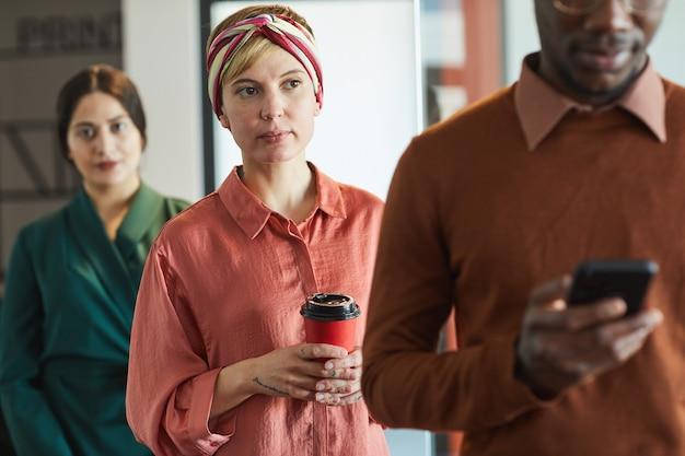 Retrato de executivos em pé na fila do escritório, foco na jovem mulher moderna segurando a xícara de café