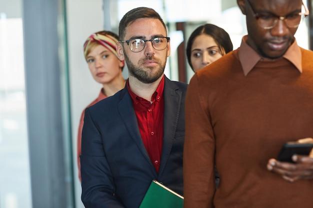 Retrato de executivos em pé na fila do escritório, foco no empresário barbudo maduro, espaço de cópia