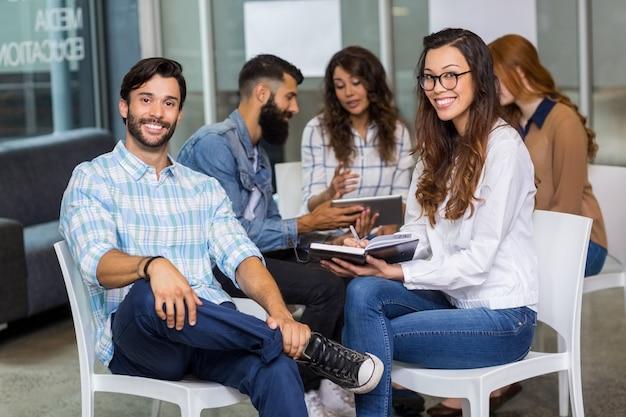 Retrato de executivos masculinos e femininos, sentado na reunião