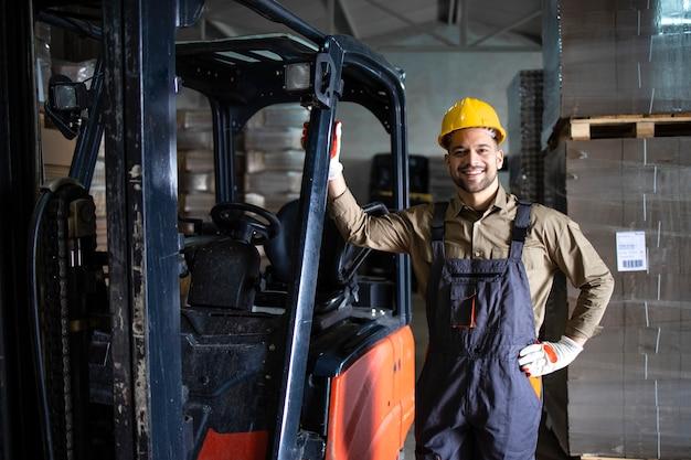 Retrato de experiente jovem motorista de empilhadeira caucasiano parado carregando a máquina de carga no armazém de armazenamento.