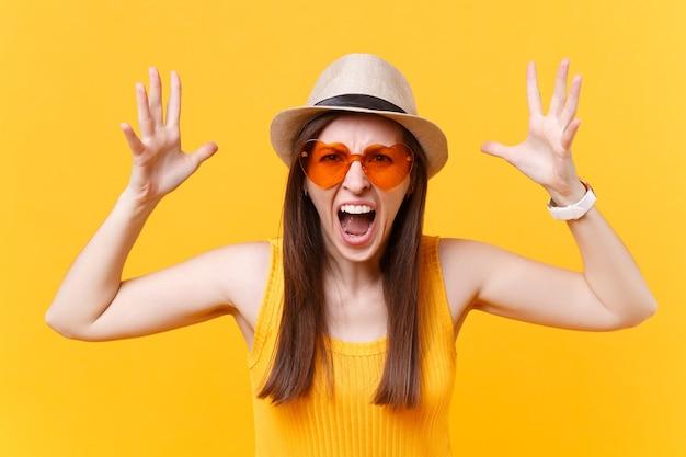 Retrato de expressiva mulher gritando em copos laranja, espalhando as mãos, mantendo a boca bem aberta, parecendo agressivo isolado em fundo amarelo. conceito de emoções sinceras de pessoas. área de publicidade.