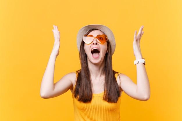 Retrato de expressiva mulher gritando triste chateada em copos laranja, espalhando as mãos, mantendo a boca bem aberta, olhando para cima isolado no fundo amarelo. conceito de emoções sinceras de pessoas. área de publicidade