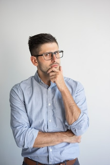 Retrato de eyeglasses desgastando do homem de negócios novo pensativo.