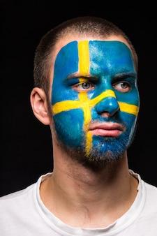 Retrato de fã de torcedor de rosto de homem bonito da seleção da suécia com o rosto de bandeira pintado isolado no fundo preto. emoções dos fãs.