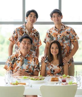 Retrato de família adorável diversão asiática, incluindo pai sênior linda mãe sentada na cadeira e dois filhos bonitos ficar atrás vestindo camisa colorida do uniforme da equipe juntos na mesa de jantar cheia de comida.