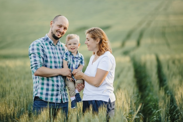 Retrato de família adorável entre o campo de vegetação