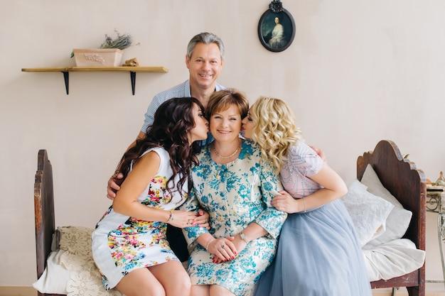 Retrato de família adulto feliz no interior vintage. pai, mãe e filhas a beijam.