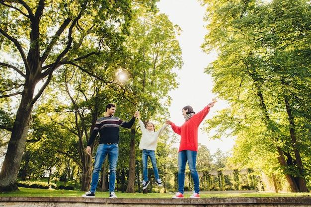 Retrato de família afetuosa amigável se divertir juntos, passar o tempo livre ao ar livre, ficar contra árvores verdes no parque