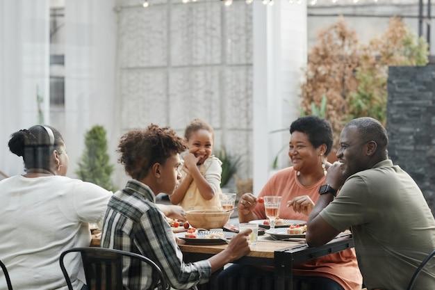 Retrato de família afro-americana, desfrutando de um jantar ao ar livre e sorrindo enquanto está sentado à mesa toget.