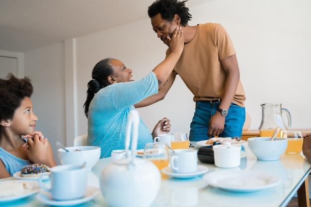 Retrato de família afro-americana, tomando café da manhã juntos em casa. conceito de família e estilo de vida.