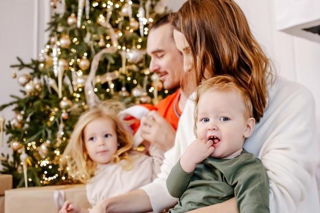 Retrato de família amigável está sentado em casa perto da árvore de natal, todo mundo está sorrindo. concentre-se no bebê.