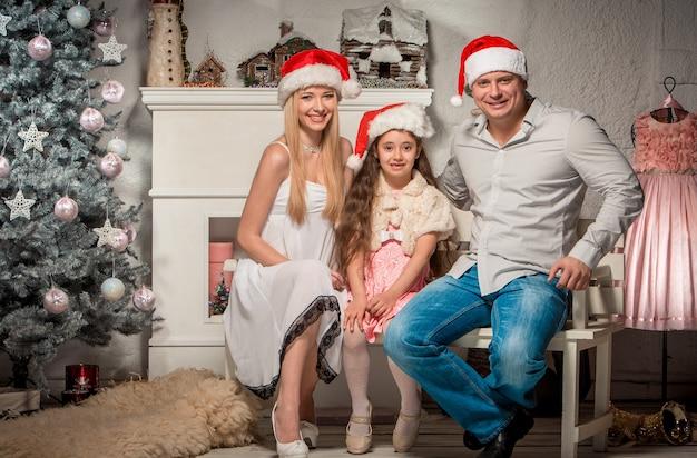 Retrato de família amigável olhando para a câmera na noite de natal