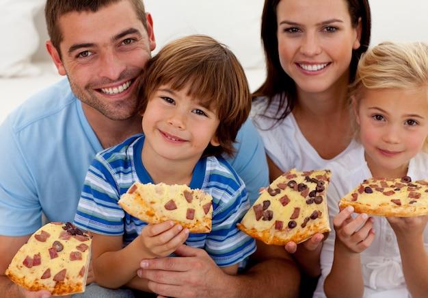 Retrato de família comendo pizza no sofá