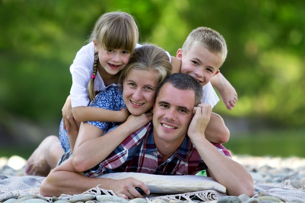 Retrato de família de jovem mãe feliz, pai e dois filhos loiros bonitos, menino e menina em dia de verão brilhante