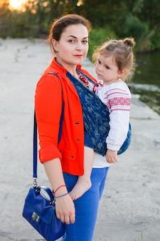 Retrato de família de mãe de negócios e menina enrolada em um estilingue azul