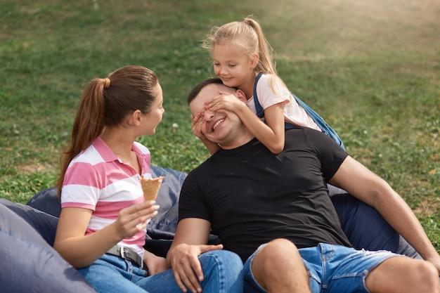 Retrato de família de mamãe, papai, filha engraçada e fofa, criança do sexo feminino cobrindo os olhos do pai com as palmas das mãos, pessoas vestindo roupas casuais