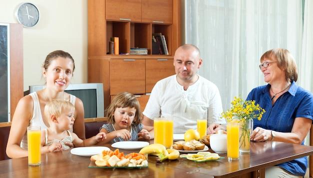 Retrato de família de multigeneração feliz comendo friuts com suco em casa juntos