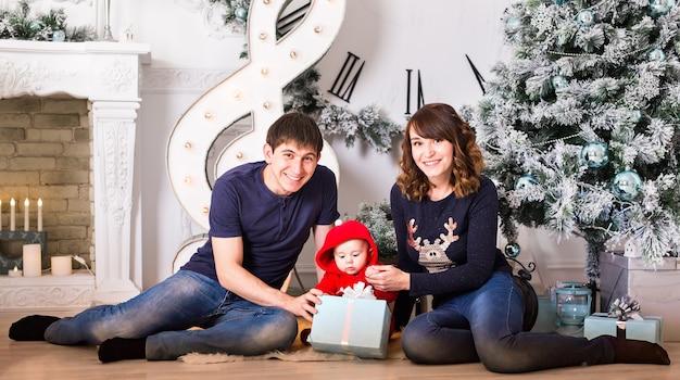 Retrato de família de natal na sala de estar de casa, caixa de presente de presente, decoração de casa por natal