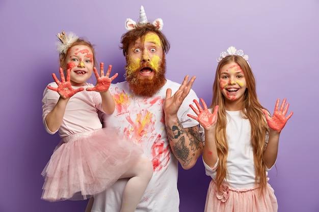 Retrato de família de pai surpreso com rosto amarelo de tintas, duas filhas alegres mostram as palmas das mãos sujas de aquarelas, quadro de pintura durante o passatempo, isolado na parede lilás. isto é arte