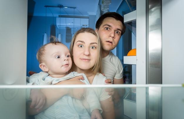 Retrato de família de pijama olhando dentro da geladeira procurando algo para comer