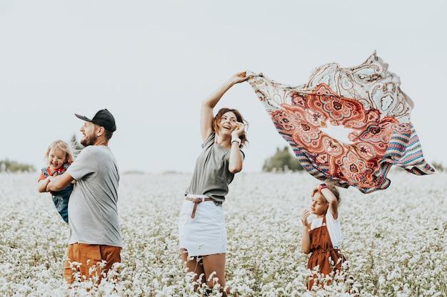 Retrato de família de um jovem casal lindo com filhos em um campo branco com flores