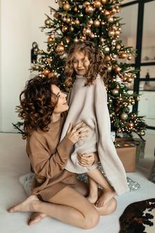 Retrato de família de uma jovem mãe atraente com uma filha vestida com roupas de malha, posando em frente a uma árvore de natal