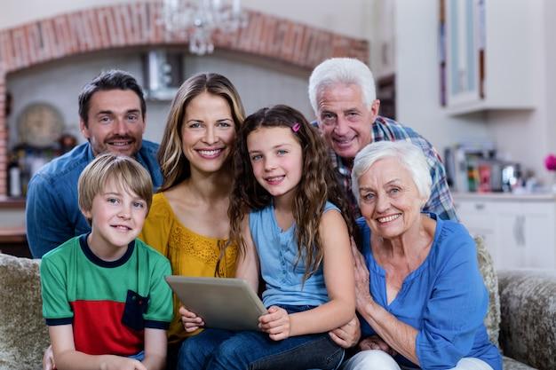 Retrato de família de várias gerações, sentado no sofá e usando tablet digital