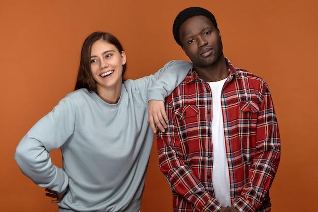 Retrato de família do lindo jovem casal interracial. imagem isolada de uma garota caucasiana animada e alegre se divertindo, apoiada no ombro do namorado, posando juntos na parede em branco