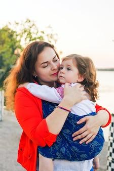Retrato de família envolvendo uma menina criança em um estilingue azul e abraços de mãe