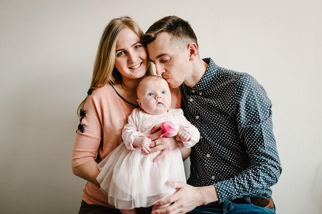 Retrato de família feliz, amor do conceito de férias em família. mãe, pai abraços filha, sentada em casa sobre um fundo claro.