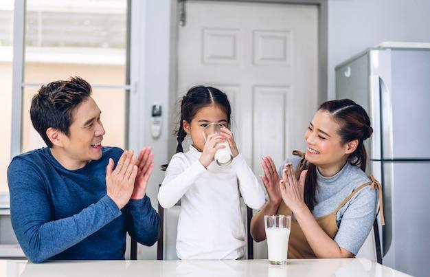 Retrato de família feliz bebendo leite na cozinha