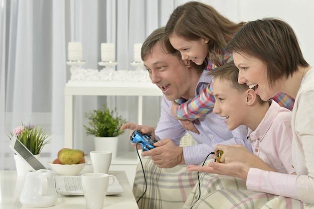 Retrato de família feliz brincando no laptop em casa