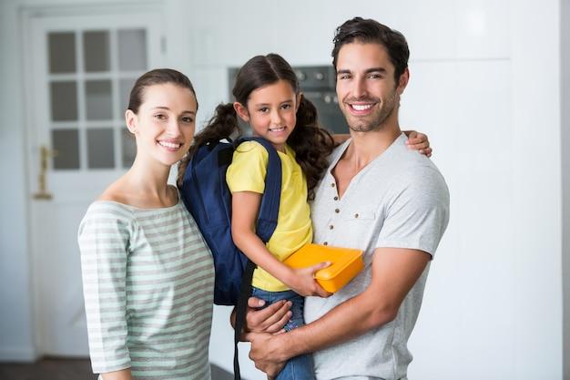 Retrato de família feliz com a filha segurando a lancheira