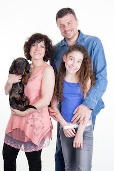 Retrato de família feliz com cachorro fofo sobre branco