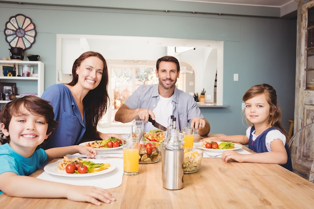 Retrato de família feliz com comida na mesa de jantar