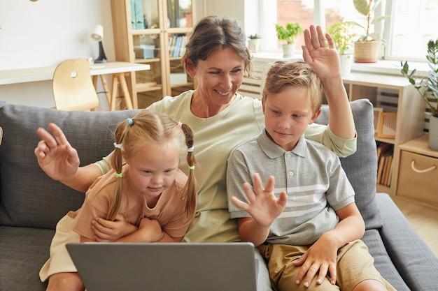 Retrato de família feliz com criança com necessidades especiais acenando para a câmera enquanto participa do bate-papo por vídeo com parentes