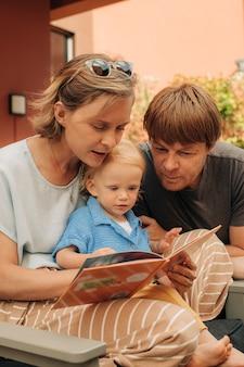 Retrato de família feliz com criança lendo livro