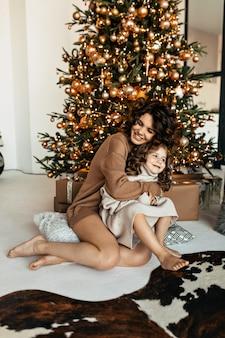 Retrato de família feliz da linda mãe com a filha vestida de suéteres de malha, sentada em frente à árvore de natal e comemorando o ano novo