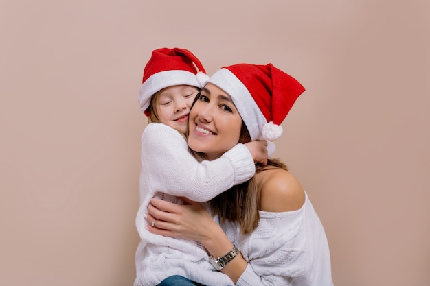 Retrato de família feliz de adorável mãe com filha se preparando para a festa de natal usando bonés de papai noel.