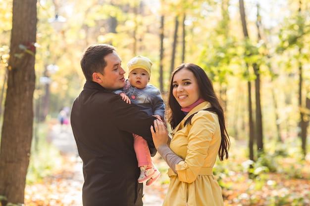 Retrato de família feliz de mãe, pai e bebê na natureza