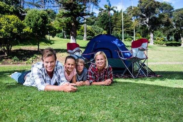 Retrato de família feliz, deitado na grama
