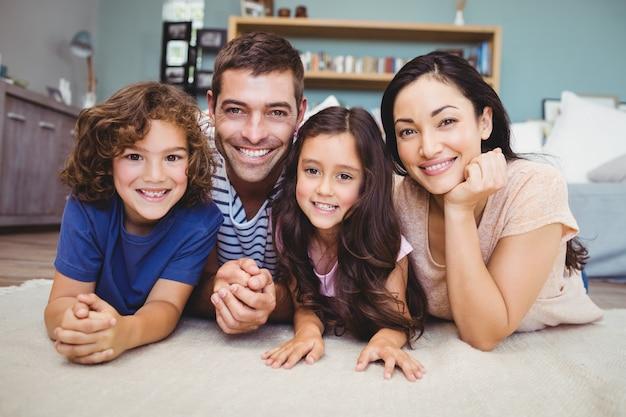 Retrato de família feliz, deitado no tapete