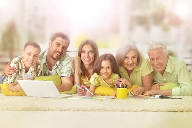 Retrato de família feliz em casa com laptop