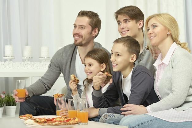Retrato de família feliz em casa com pizza