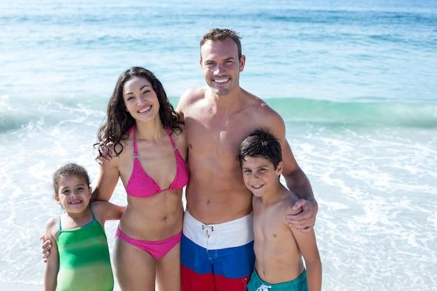 Retrato de família feliz em pé na praia