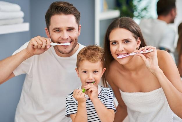 Retrato de família feliz escovando os dentes no banheiro