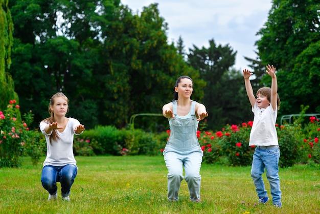 Retrato de família feliz fazendo exercícios físicos ou fitness no parque